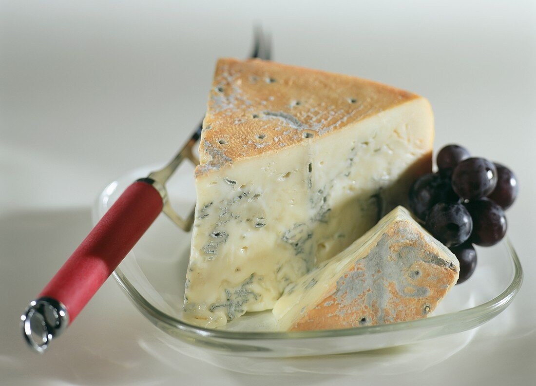 A piece of gorgonzola picante with grapes & cheese knife