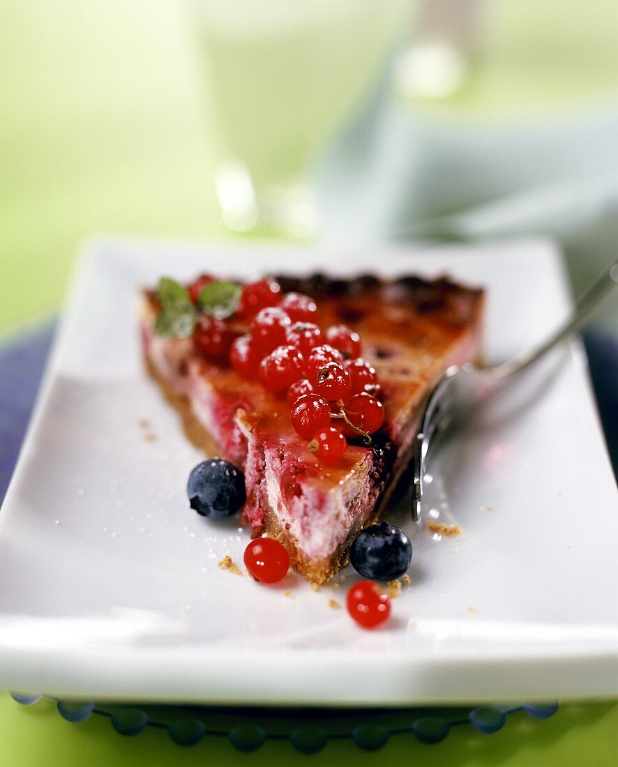 A piece of redcurrant and blueberry tart