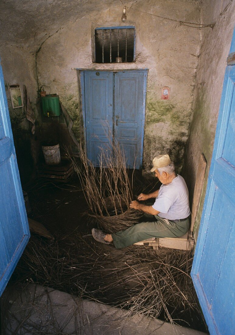 Old man weaving basket from thin branches, Santorini