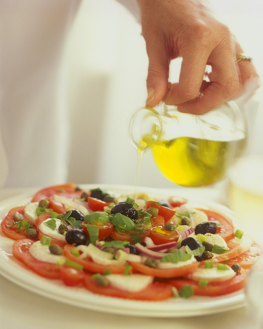 Sprinkling mozzarella on tomatoes (caprese) with olive oil