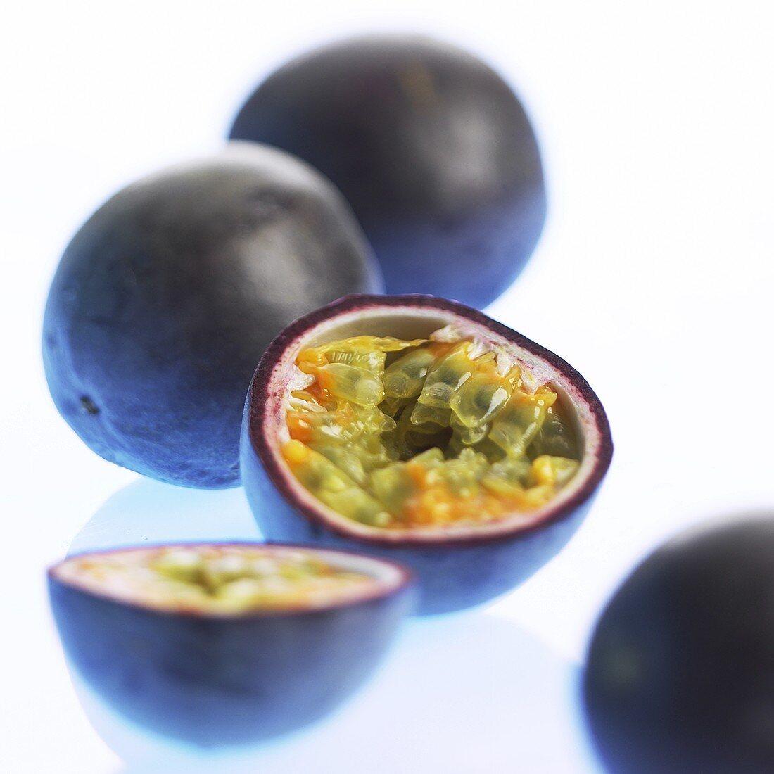 Passion fruits (purple granadilla), whole and halved
