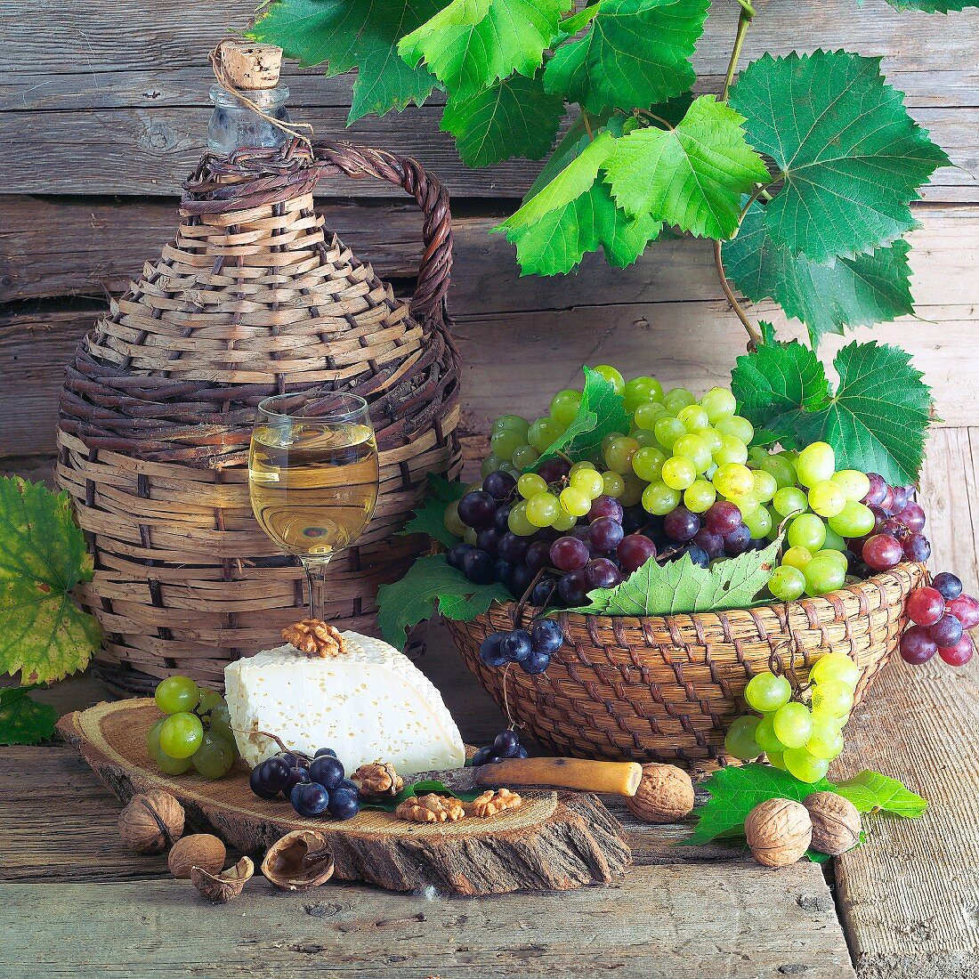 Still life with white wine, grapes, cheese and walnuts