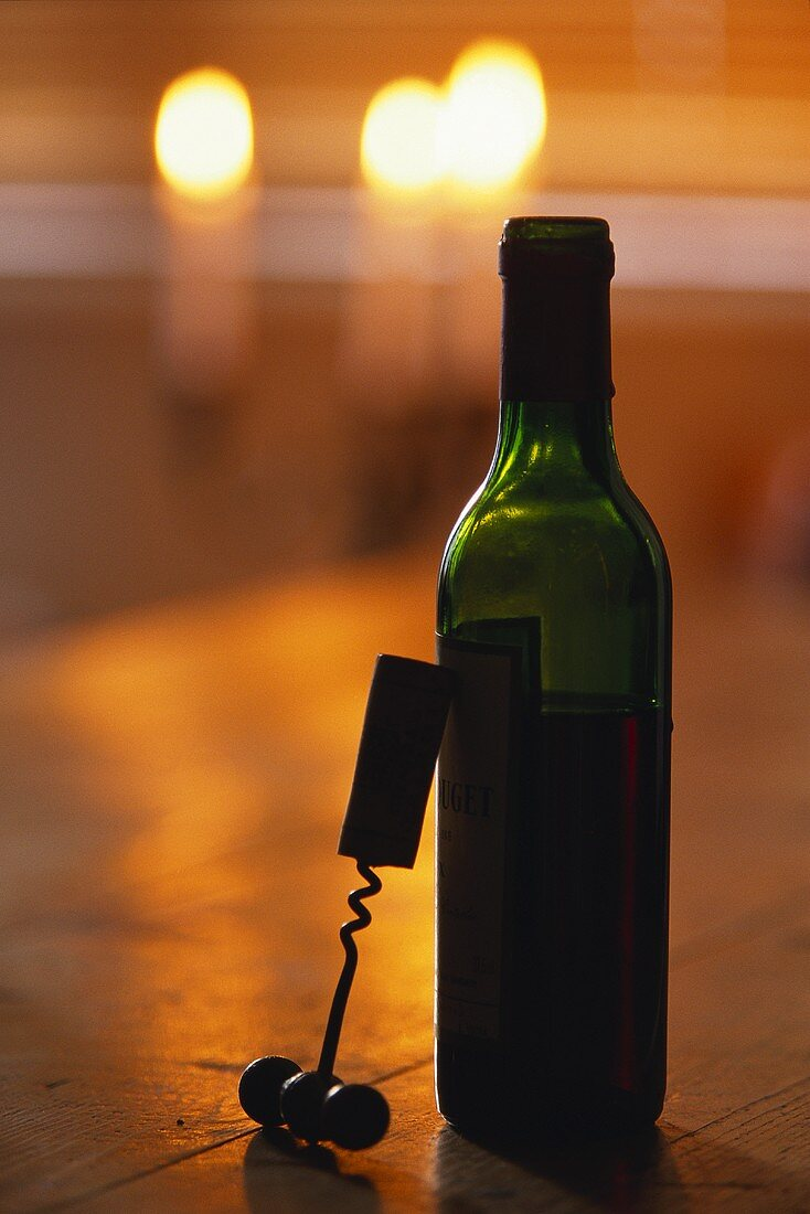 Corkscrew leaning on red wine bottle; burning candles