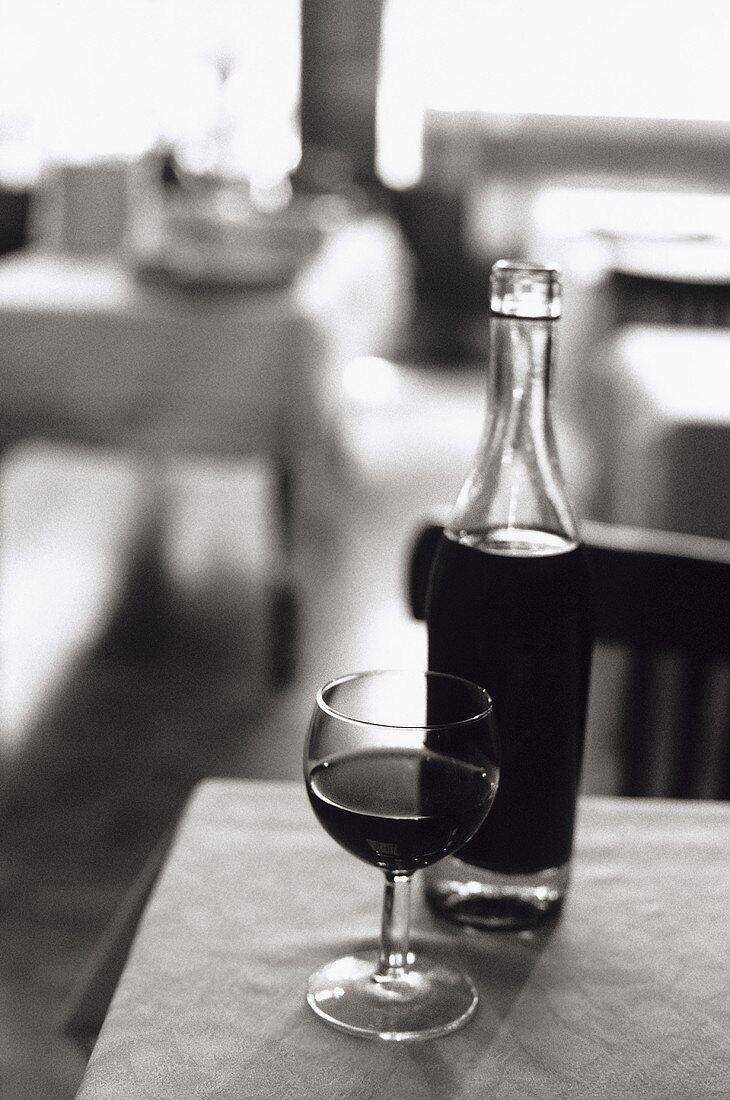 Pot lyonnais (typical Lyon wine bottle) with glass in bistro