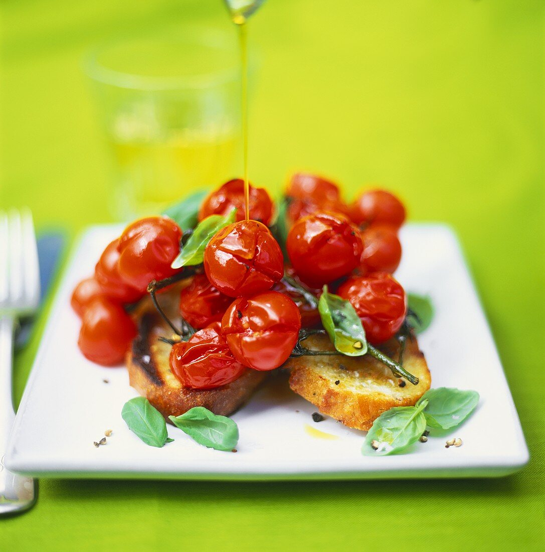 Drizzling olive oil over baked tomatoes on toast