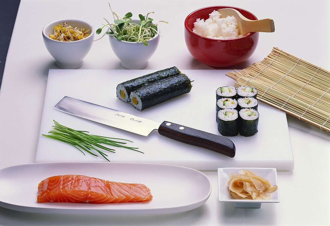 Still life with maki-sushi, sushi knife and ingredients
