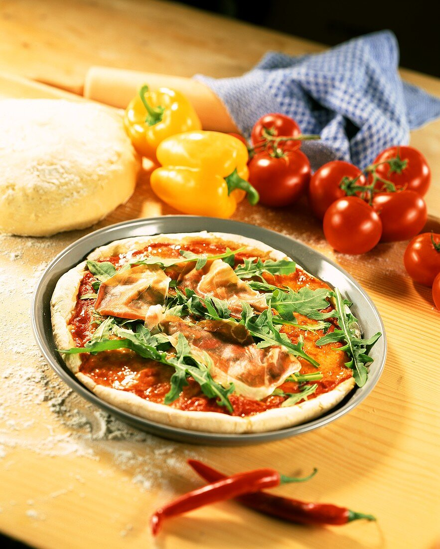 Pizza with tomato sauce, rocket and ham before baking