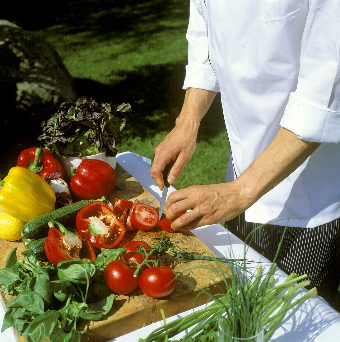 Chef cutting fresh vegetables and herbs (outdoor shot)