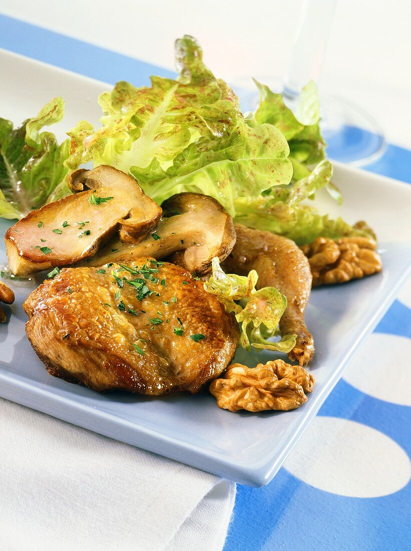 Quail breasts on oak leaf lettuce with nuts and ceps