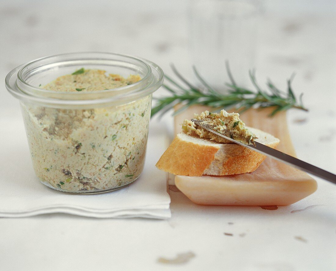 Spreading turkey sausage with herbs in preserving jar
