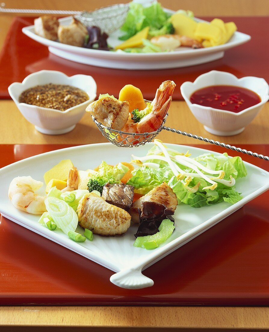 Fondue chinoise with meat, chicken, fish and sauces