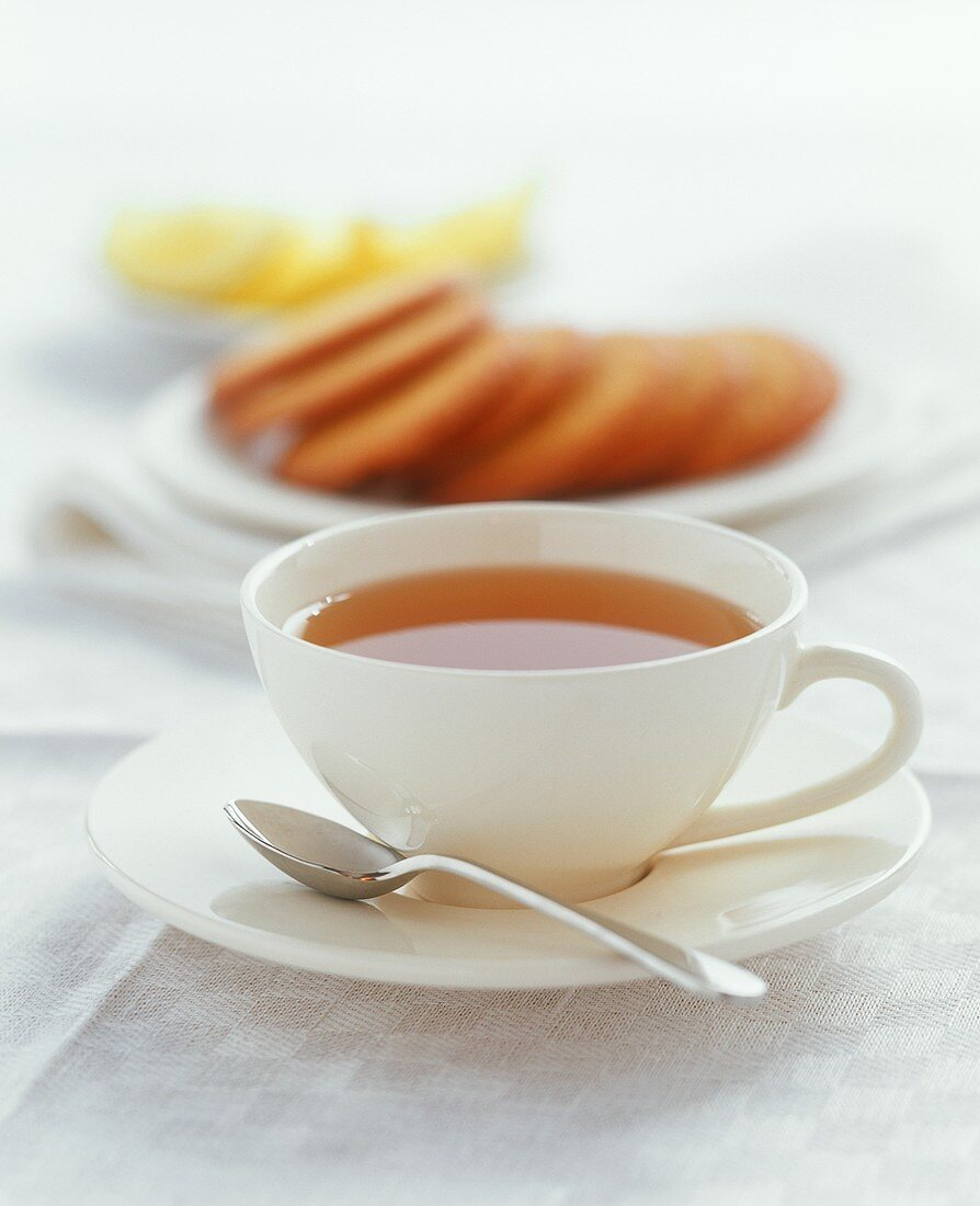 Cup of tea with biscuits in background
