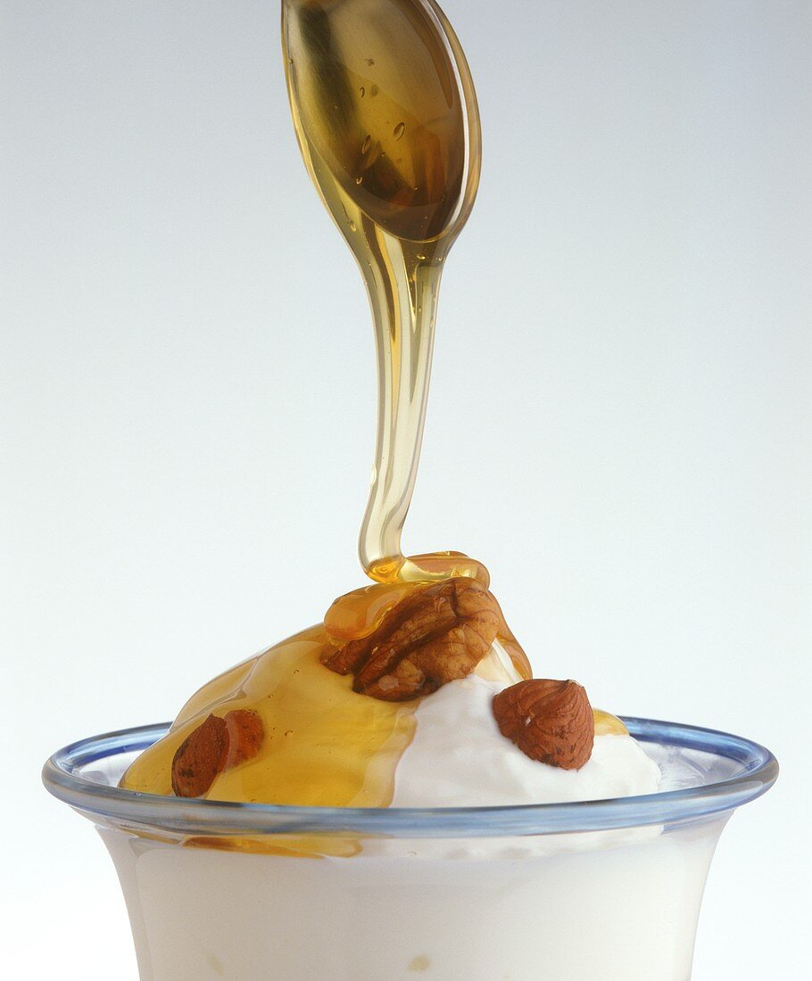 Natural yoghurt with nuts and honey (running from spoon)