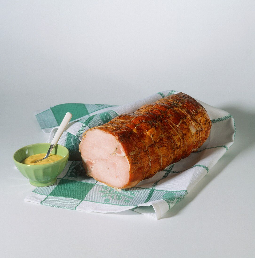 Cold roast pork roll on kitchen cloth with bowl of mustard