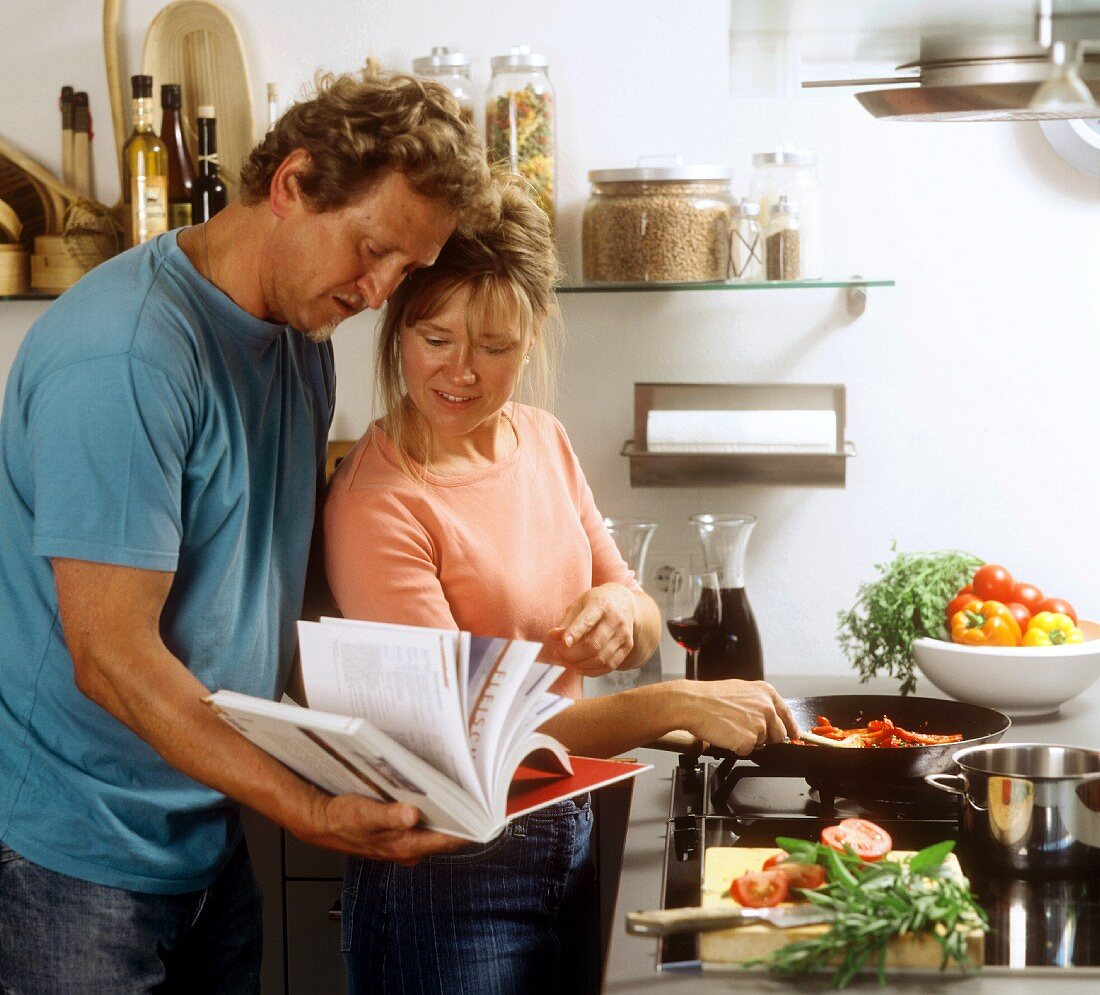 Kitchen scene: man and woman looking for recipe in cookbook