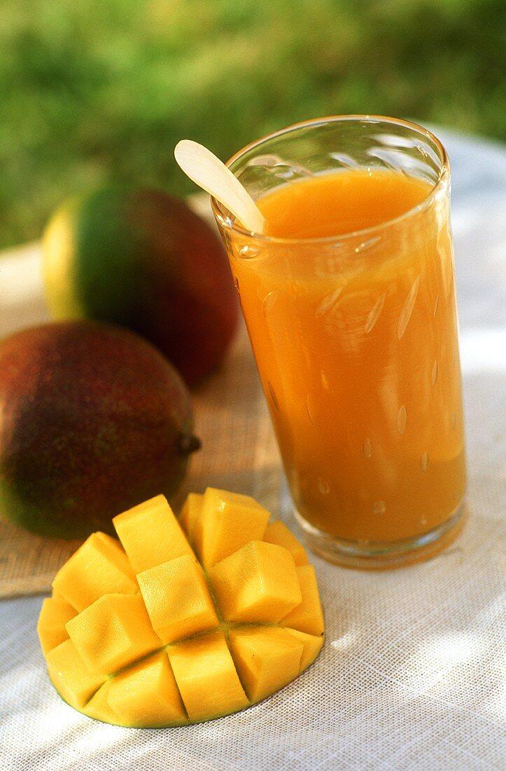 Glass of mango juice, whole mangos and one cut open