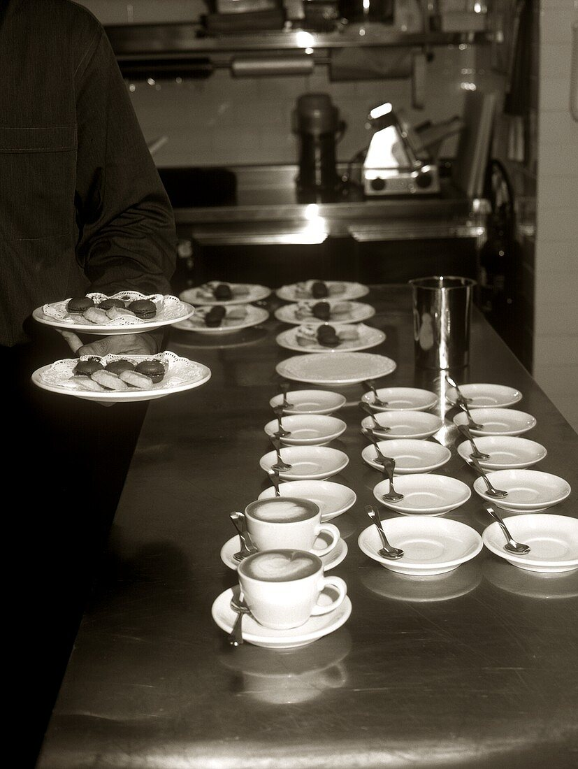 Coffee cups and plates of biscuits in restaurant kitchen