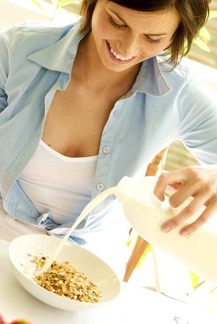 Woman pouring milk into a bowl of oat muesli
