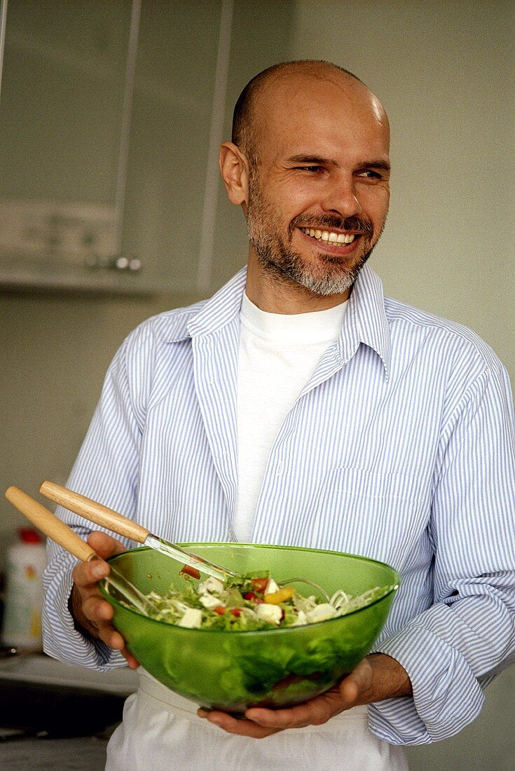 Man holding a dish of mixed salad with sheep's cheese