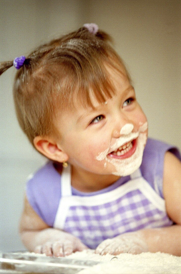 Small laughing girl baking with flour on her face