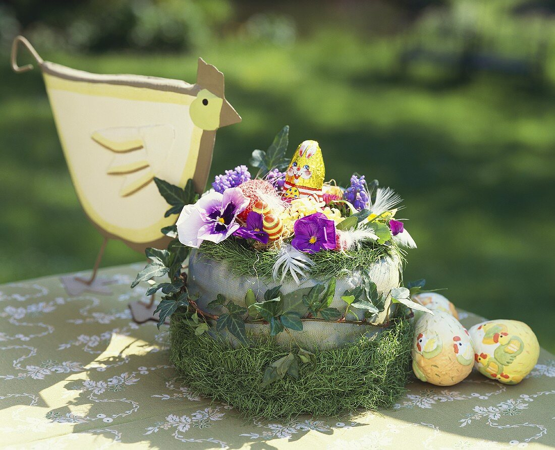 Easter nest with spring flowers, ivy, grass, chocolate bunny