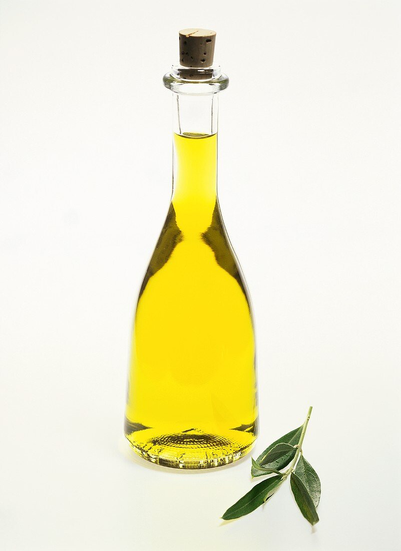 Olive oil in bottle with cork and olive branch