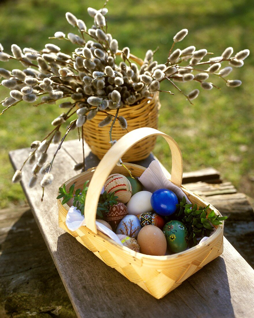 Basket of coloured Easter eggs in front of pussy willow