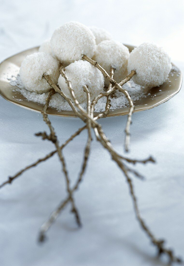 Almond coconut balls stuck on branches