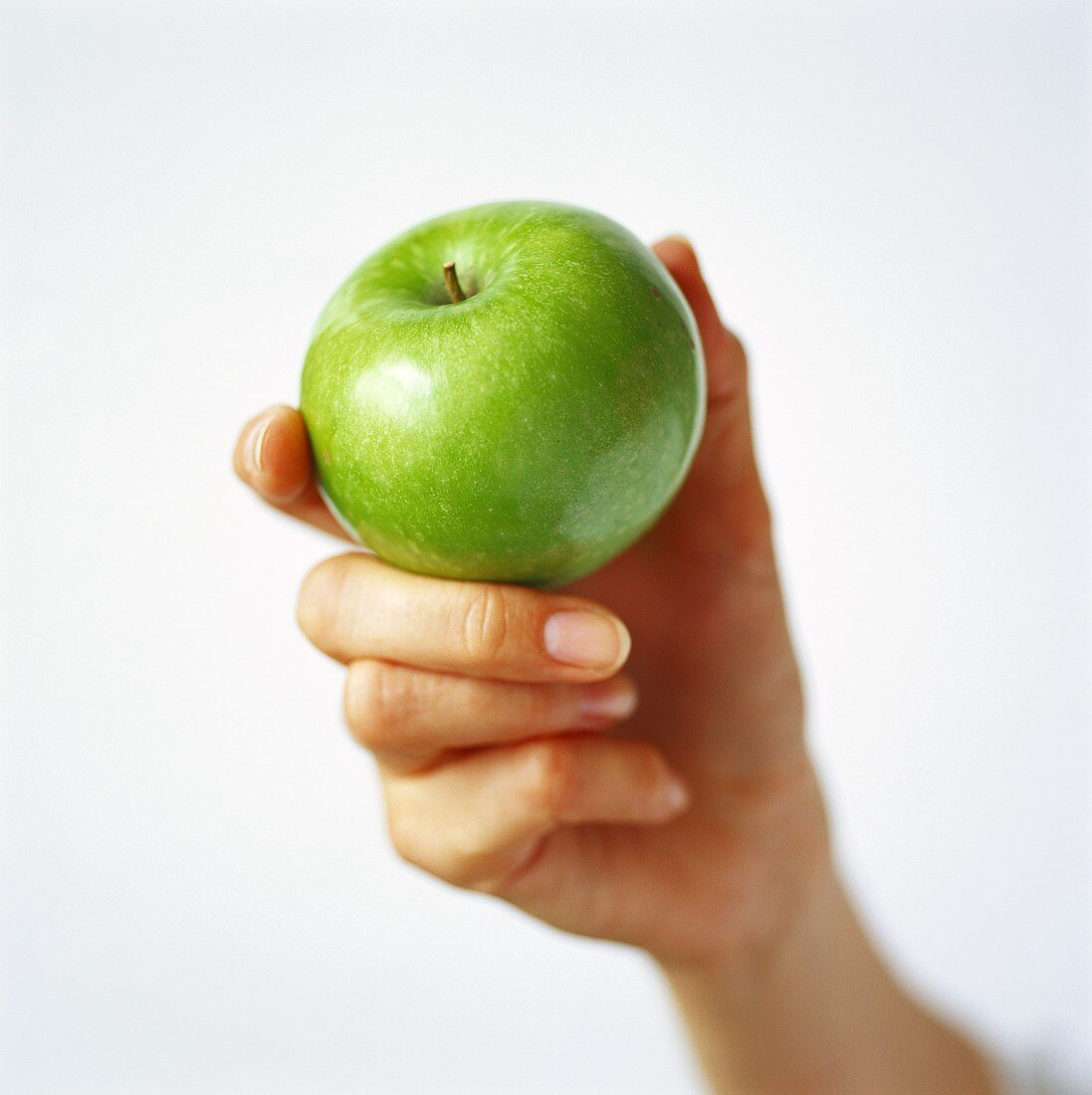 Hand holding a green apple