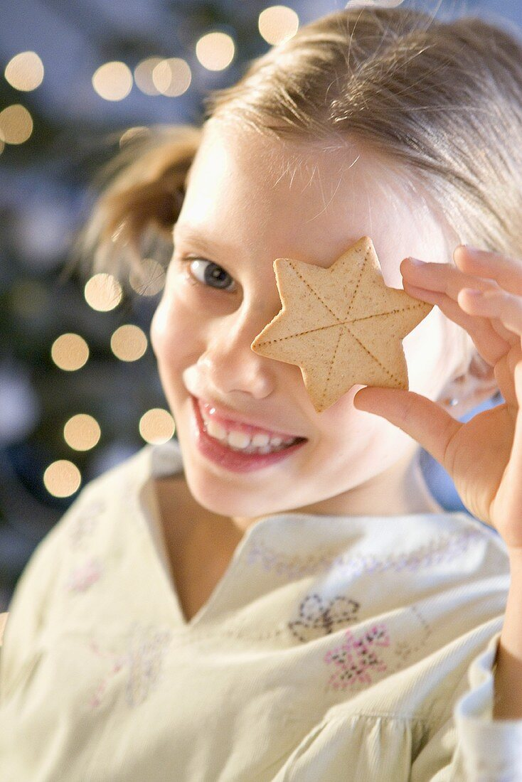 Smiling girl holding star biscuit in front of her eye