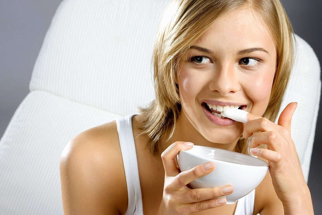 Young woman with bowl of yoghurt, licking her finger
