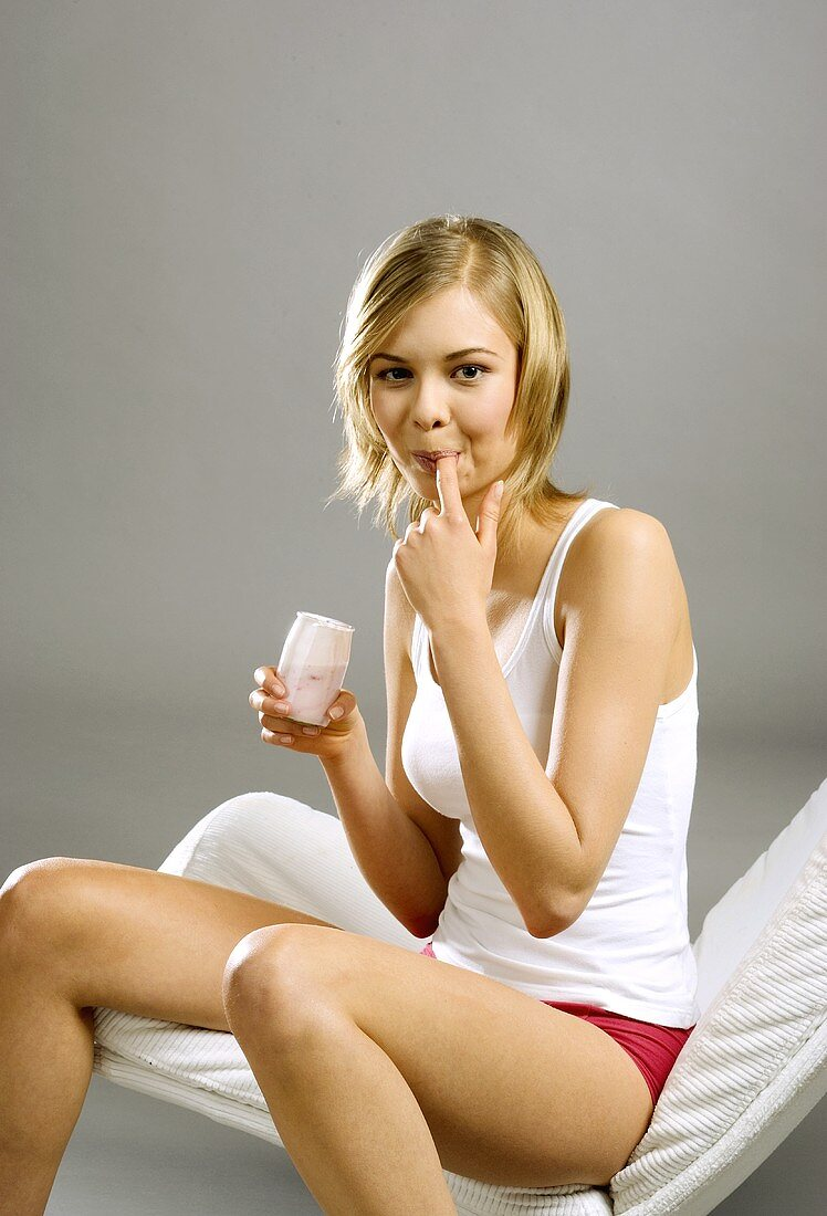Young woman, seated, with yoghurt jar, licking her finger
