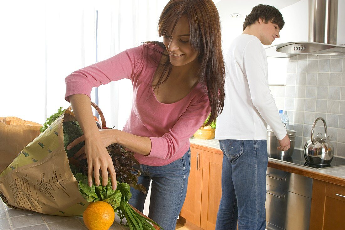 Young couple standing in kitchen, woman unpacking shopping