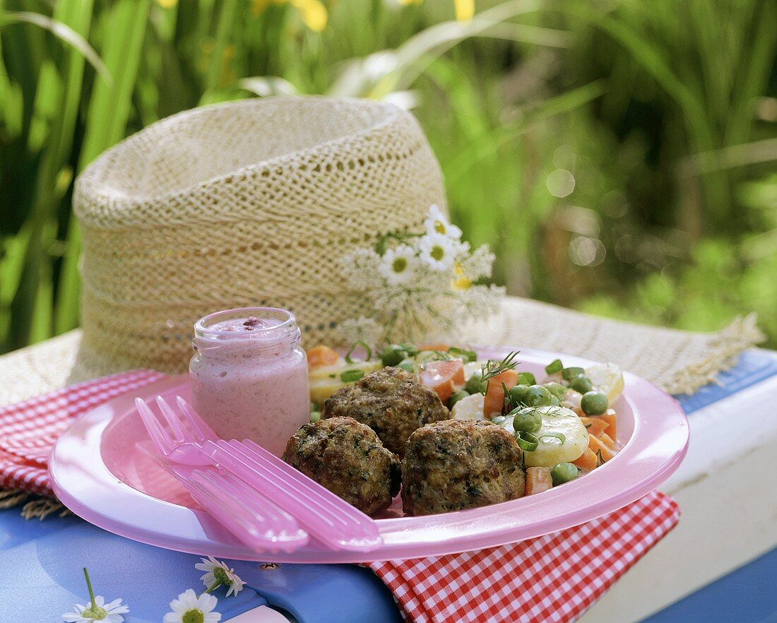 Picnic plate with fried meatballs in open air