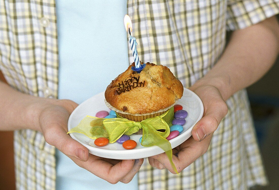 Boy holding muffin with burning birthday candle