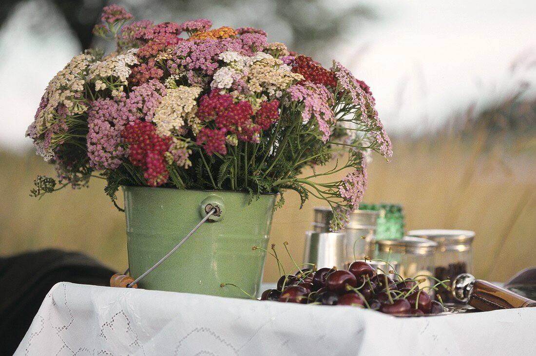 Table in open air with flowers and cherries