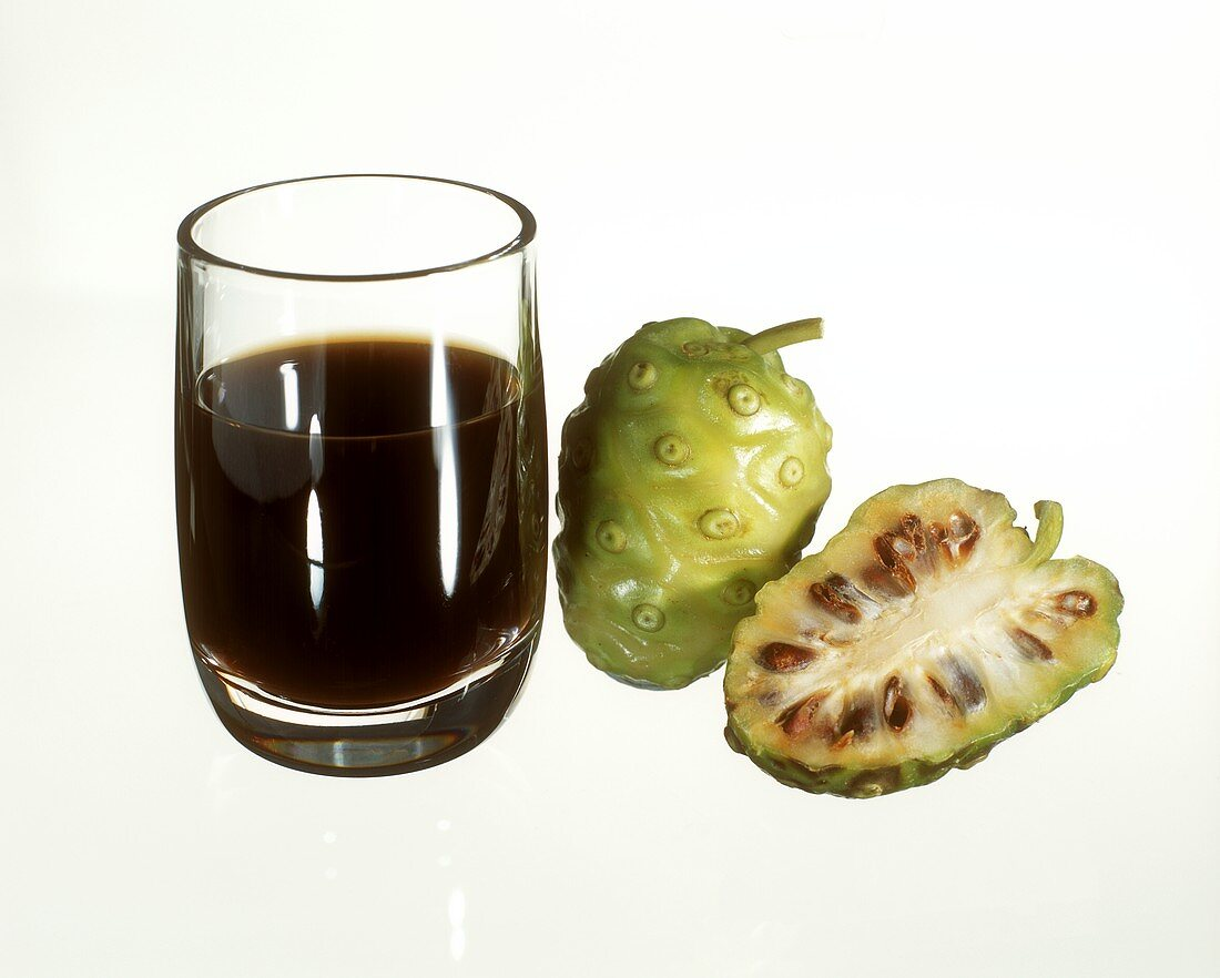 Glass of noni juice and noni fruit