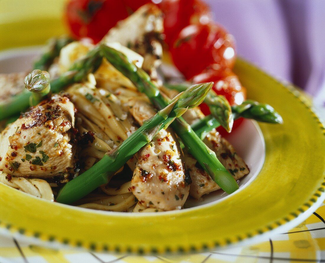 Marinated chicken breast filet with green asparagus on linguine
