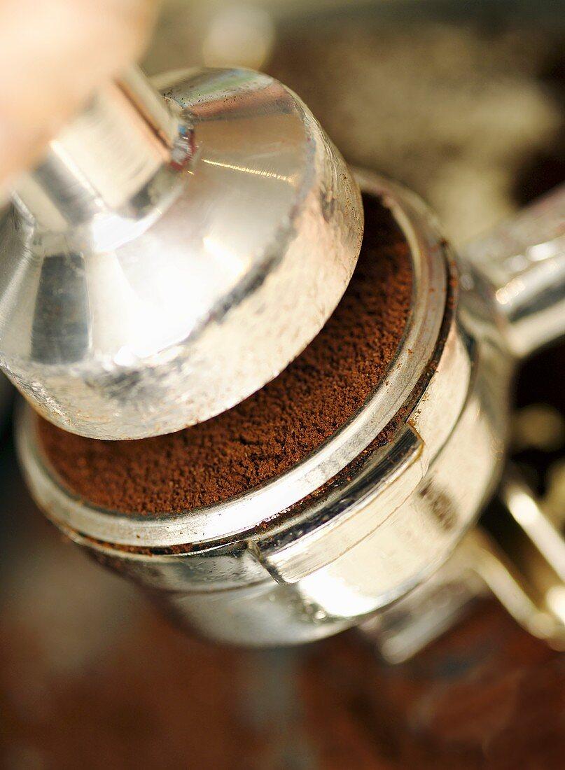 Espresso powder being pressed into a portafilter (close-up)