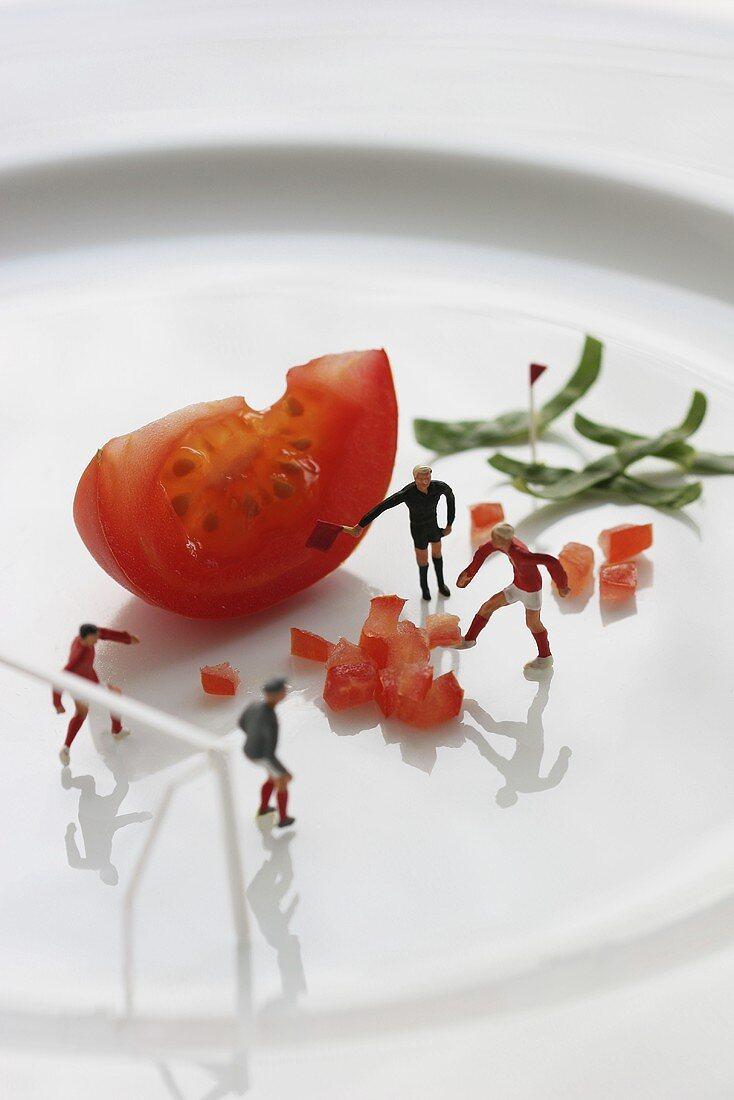 Miniature footballers training on plate of diced tomatoes
