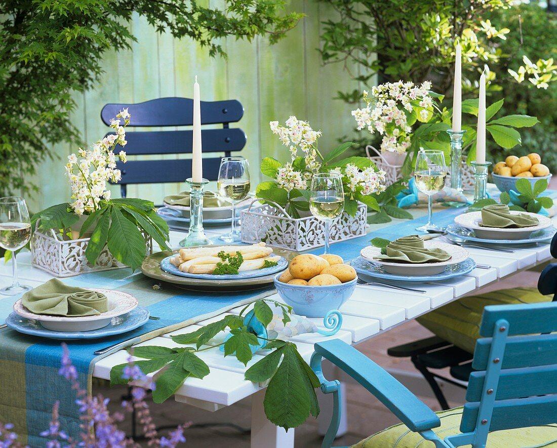 Gedeckter Tisch mit Spargel und Kastanienblüten dekoriert