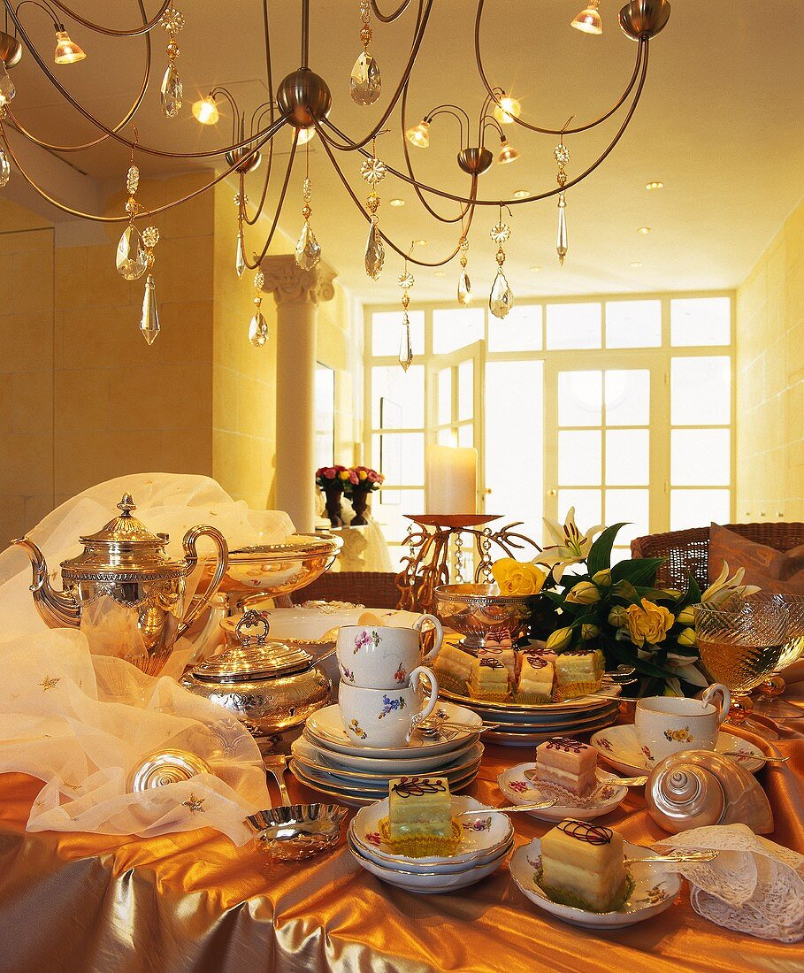 Table laid for coffee with nostalgic tableware & cakes