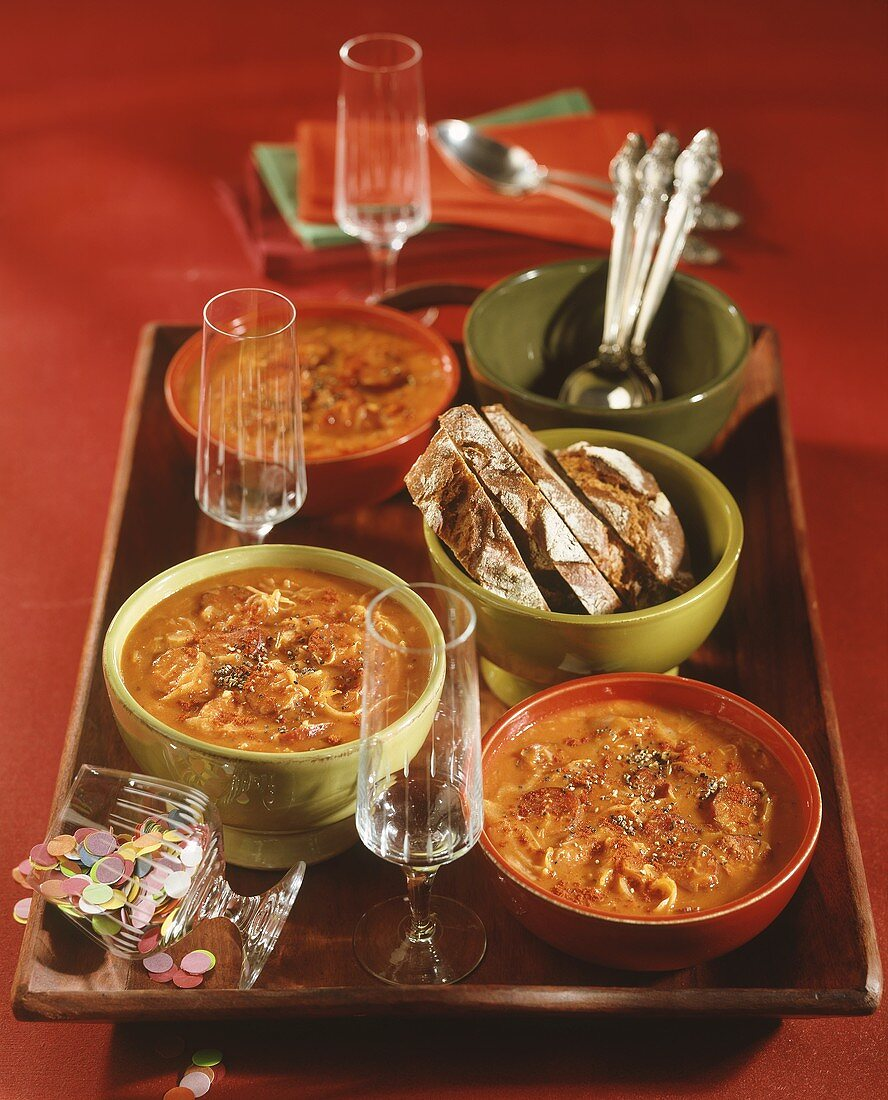 Spicy cabbage soup with bread on a tray for New Year's Eve