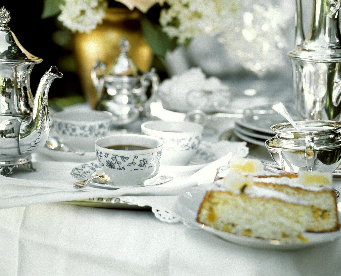 Elegant table laid for coffee in garden with cakes and coffee