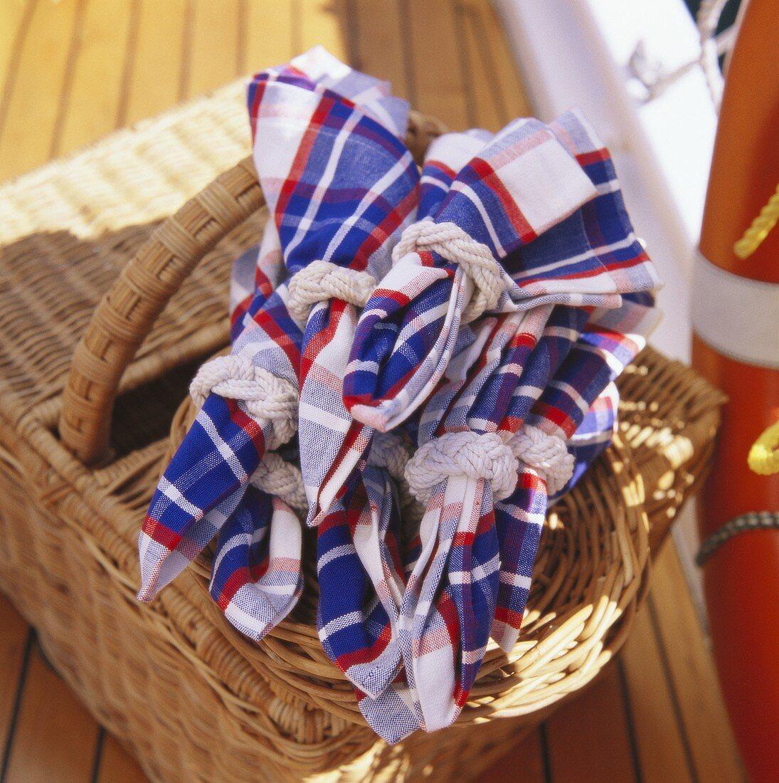 Folded fabric napkins on picnic basket on boat