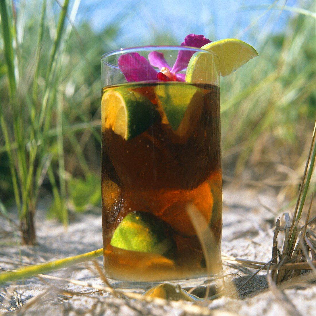 Cuba libre (rum drink with cola) in sand