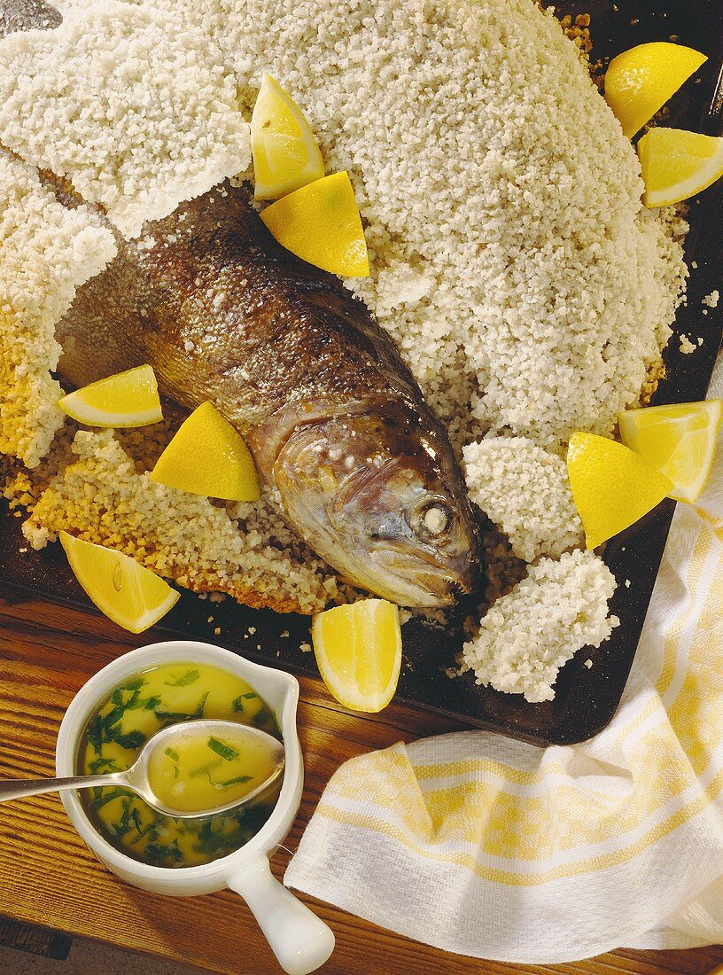 Salmon trout in sea salt crust with pieces of lemon