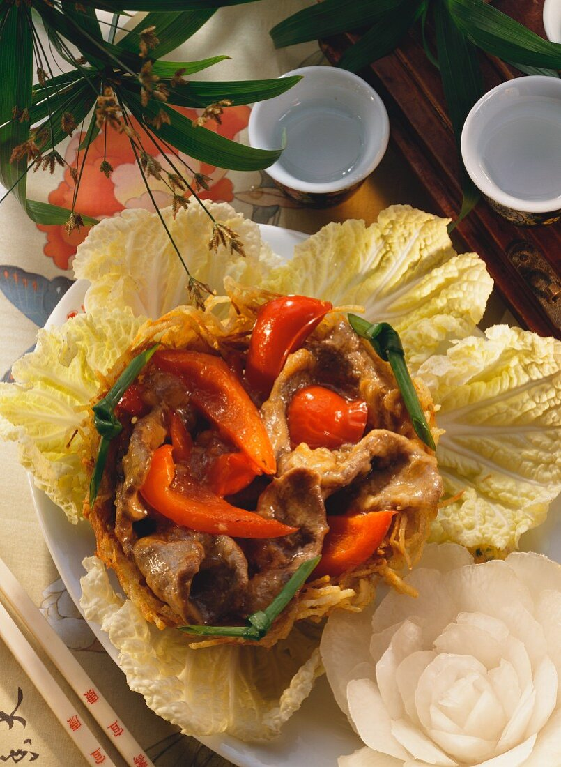 Meat with peppers in potato nest on Chinese cabbage