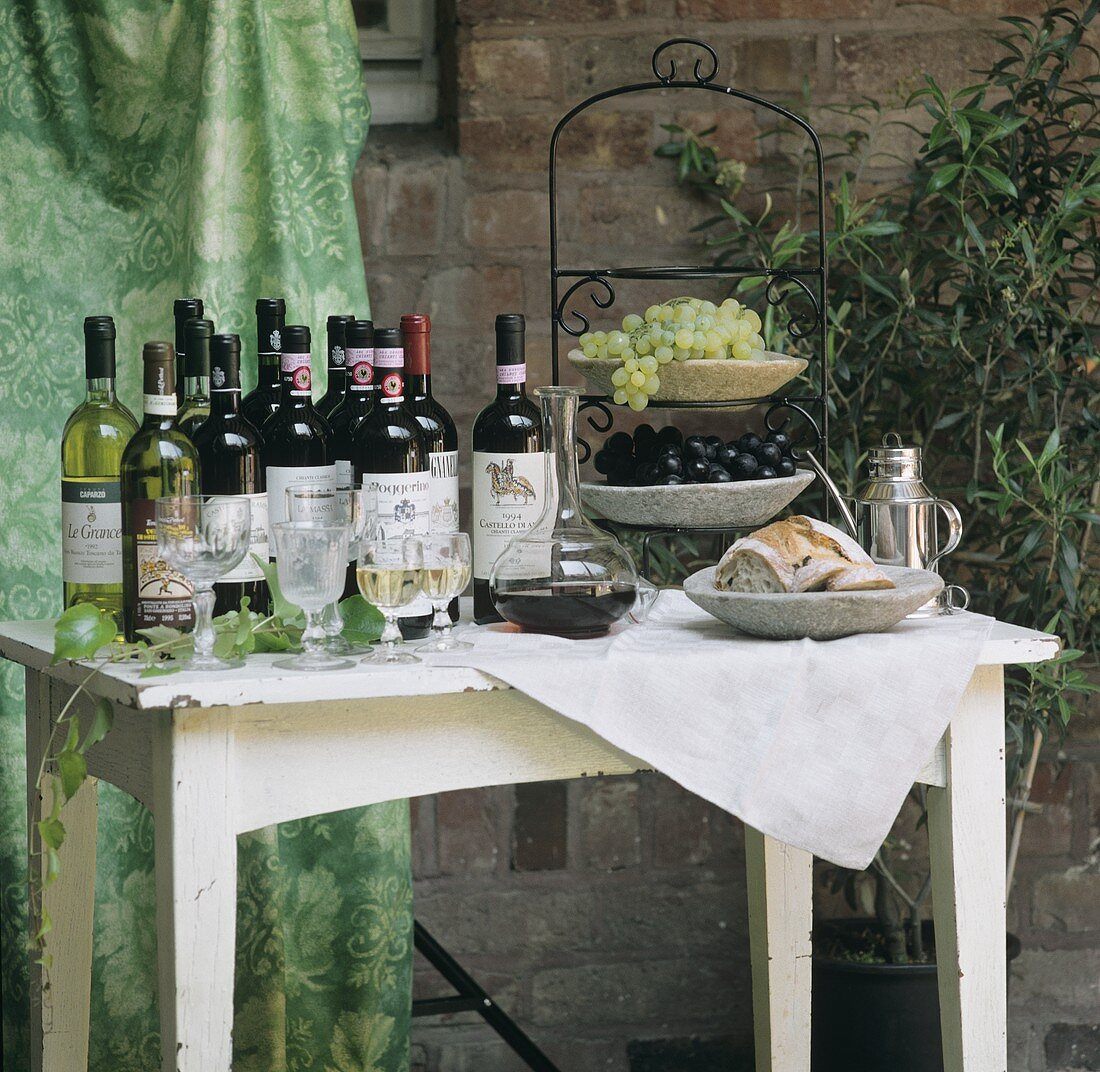 Various wine bottles, grapes on tiered stand & bread