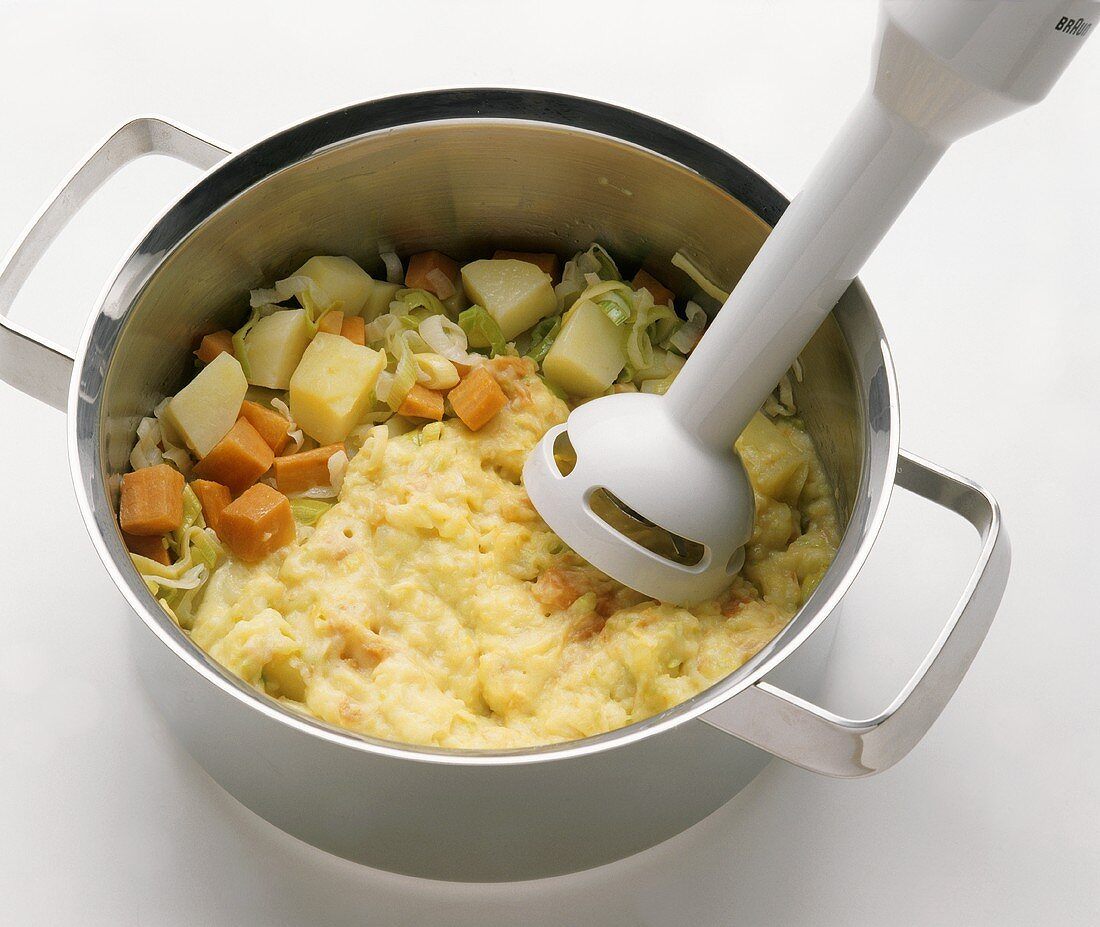 Chopping soup vegetables in pan with hand blender
